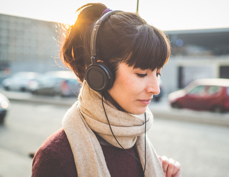 An image of a girl listening to hire headphones