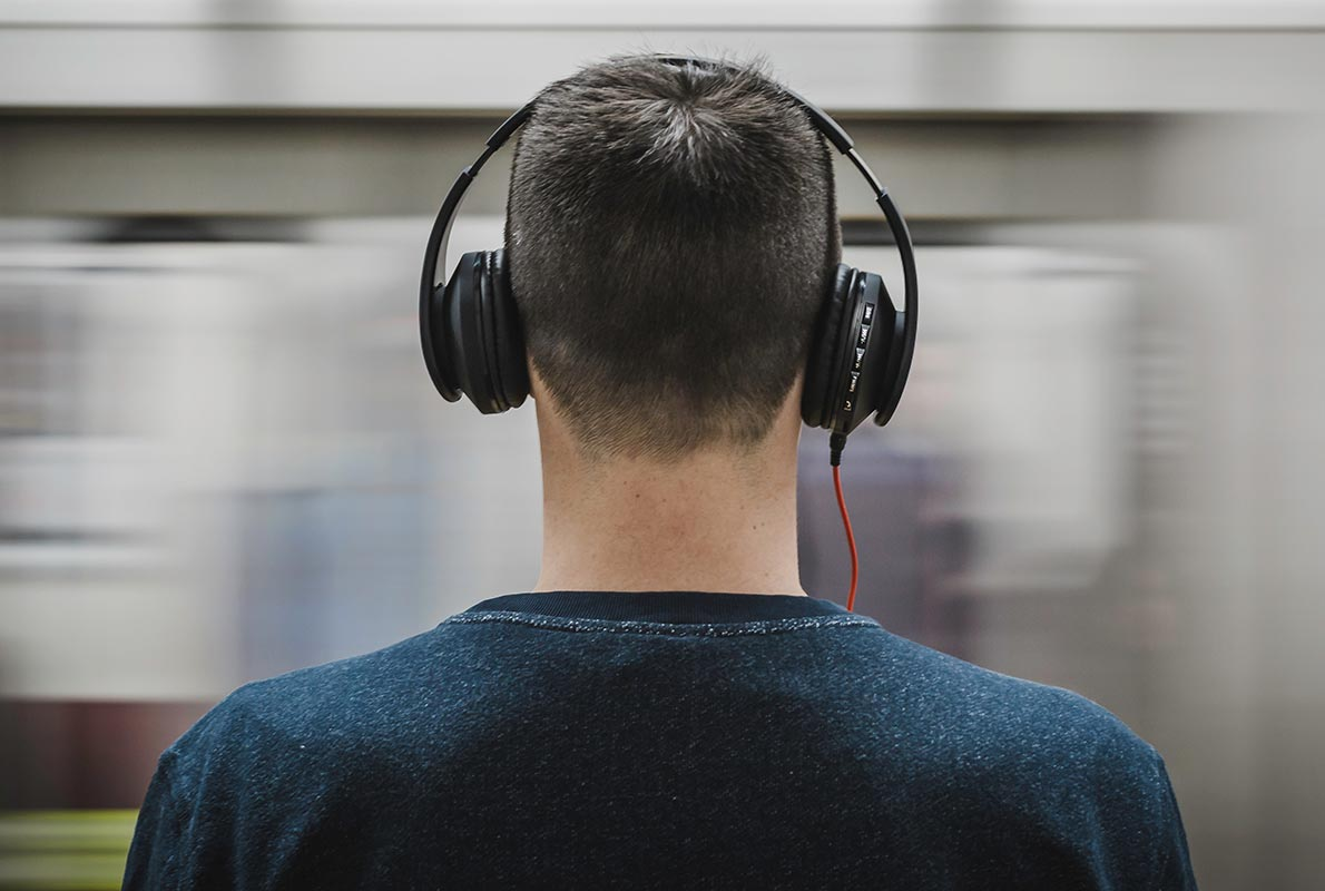 An image of a man attempting Noise reduction in a busy subway with headphones